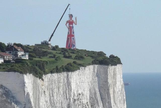 A giant scaffolding sculpture with an image of Britain's Prime Minister wearing the Union Flag and making a gesture towards continental Europe is seen on top of the cliffs overlooking the south coast of England and the Channel